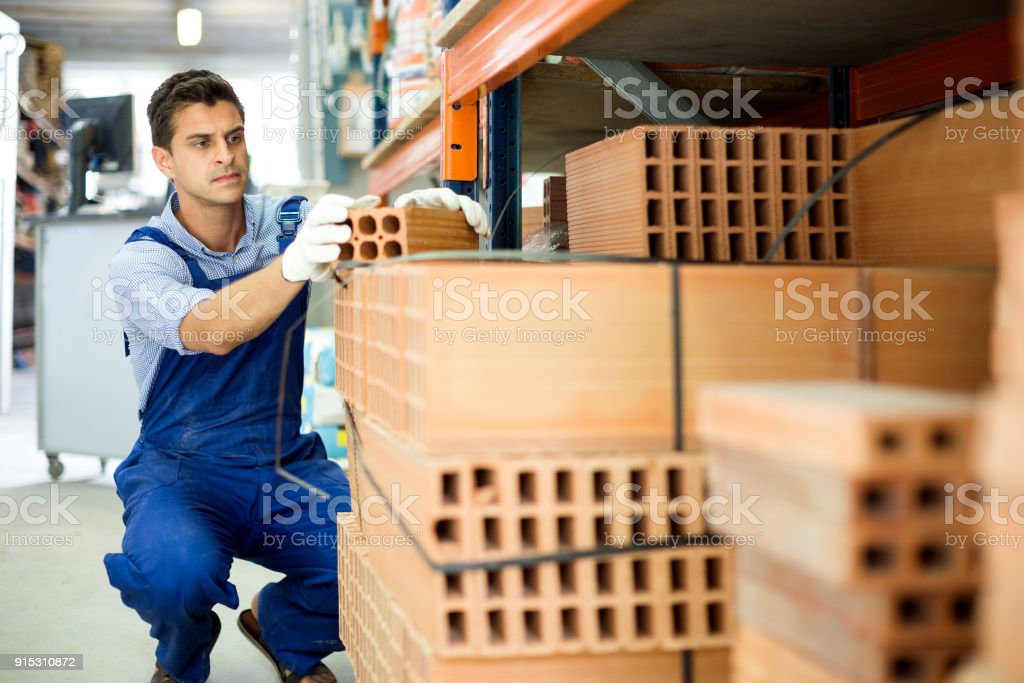 Shop assistant man is checking quality of bricks royalty-free stock photo