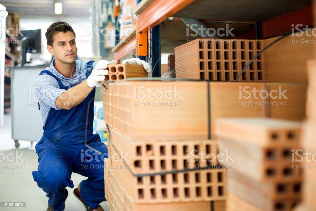 Assistente de loja homem está verificando a qualidade dos tijolos - foto de acervo