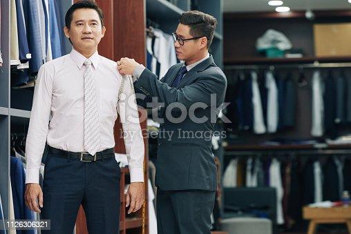 istock Shop assistant measuring customer 1126306321
