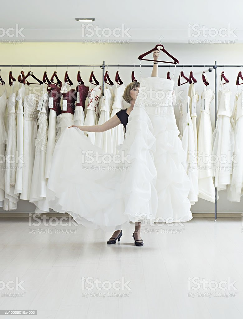 Shop assistant showing wedding dress in shop foto de stock royalty-free