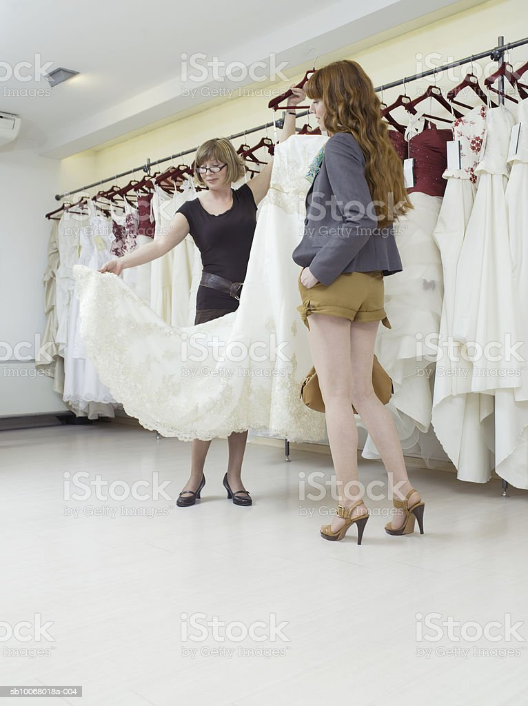 Shop assistant showing wedding dress to young woman royalty free stockfoto