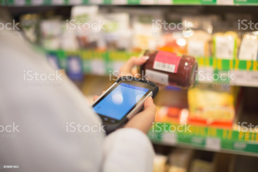 Shop assistant using barcode reader stock photo