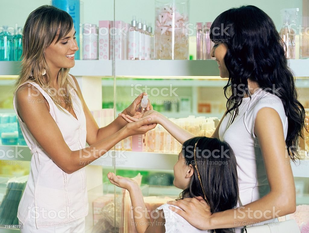 Shop assistant with mother and daughter royalty-free stock photo