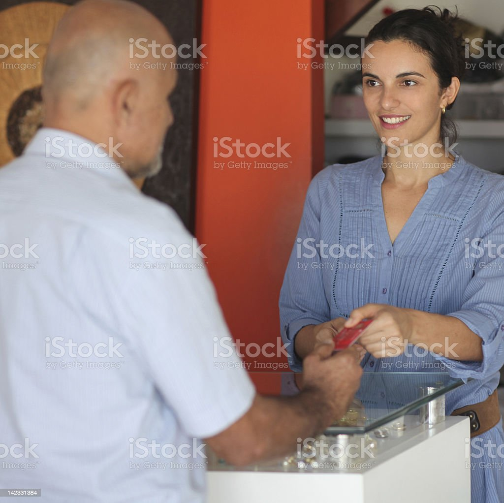Shop assistent accepting a credit card royalty-free stock photo