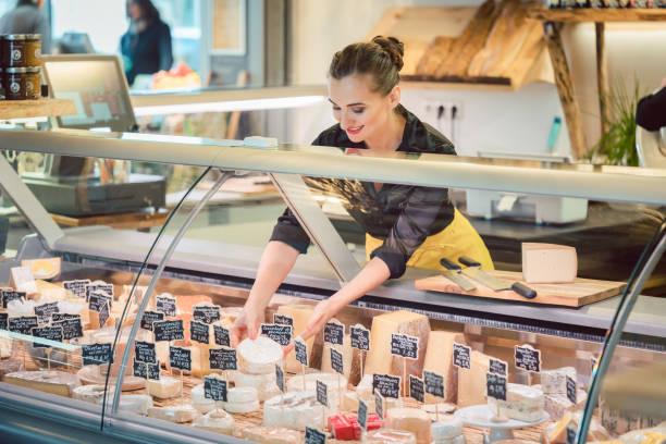 mujer de vendedor de tienda clasificación queso en la exhibición del supermercado - tienda delicatessen fotografías e imágenes de stock