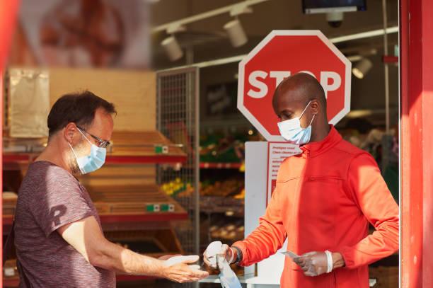 Shop-Mitarbeiter am Eingang des Supermarktes Sprühdesinfektionsmittel auf Kundenhände für Sicherheitsmaßnahmen während covid-19 – Foto