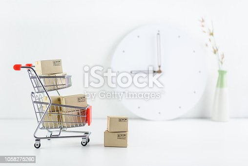 868776578 istock photo Shop online, ecommerce / retail commerce concept : Box or cartons in a trolley or shopping cart on a seller working desk / office table, depicts new lifestyle customers buy products via online store. 1058275260