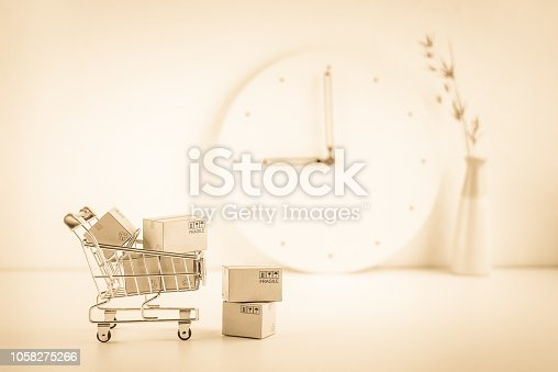 868776578istockphoto Shop online, ecommerce / retail commerce concept : Box or cartons in a trolley or shopping cart on a seller working desk / office table, depicts new lifestyle customers buy products via online store. 1058275266