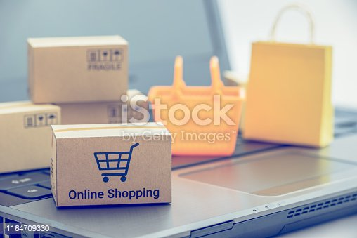 868776578 istock photo Shop online, ecommerce / retail commerce concept : Box or cartons with trolley or shopping cart, shopping basket on a laptop computer, depicts new lifestyle customers buy products via online store. 1164709330