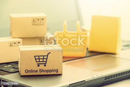868776578 istock photo Shop online, ecommerce / retail commerce concept : Box with shopping cart and words online shopping, shopping basket, shopping bag on a laptop computer, depicts customers buy products via online store 1058276480