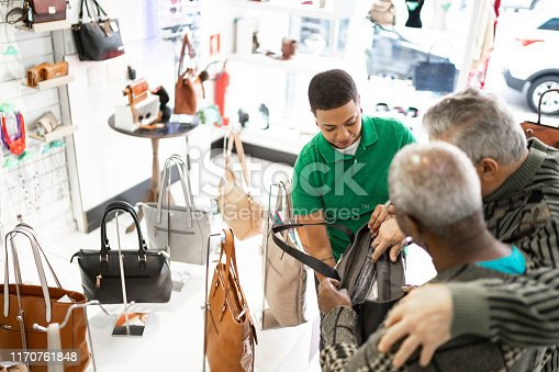 Shop owner helping woman choosing a purse, showing options