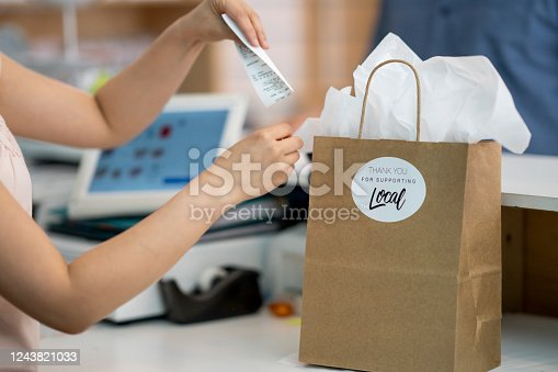 Retail worker placing debit receipt in a paper shopping bag  with a