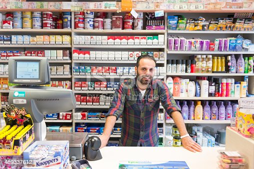 Color image of an ethnic shop owner in Amsterdam. He is standing in front of various products. Copy space above, right and left.