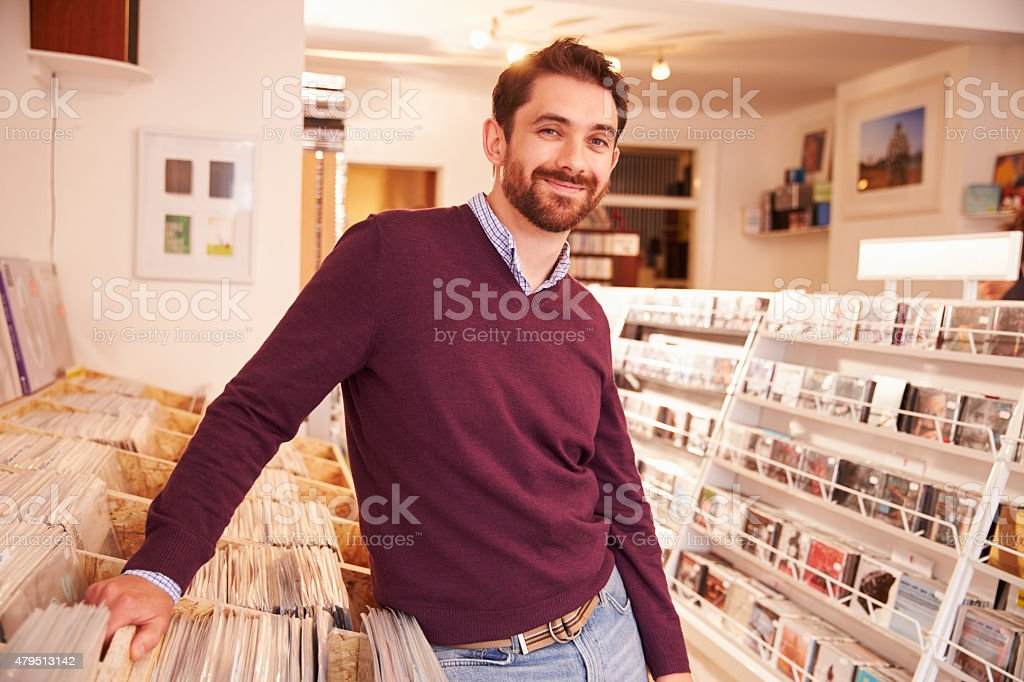 Shop owner posing in a record shop, smiling stock photo