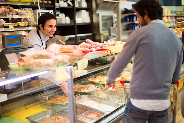 shop owner serving a customer some food - delis stock photos and pictures