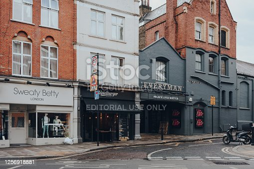 London, UK - July 02, 2020: Shop, restaurant and Everyman cinema on an empty Hampstead street in the rain. Hampstead is an affluent residential area of London favoured by artists and media figures.