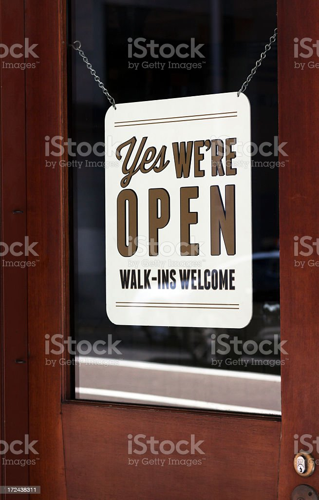 Shop sign 'YES WE'ARE OPEN' hanging on shop glass door royalty-free stock photo