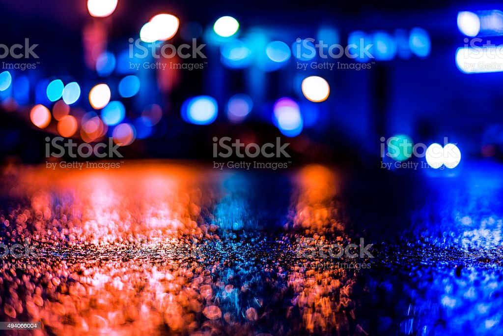 Shop windows are reflected on the wet asphalt after rain stock photo