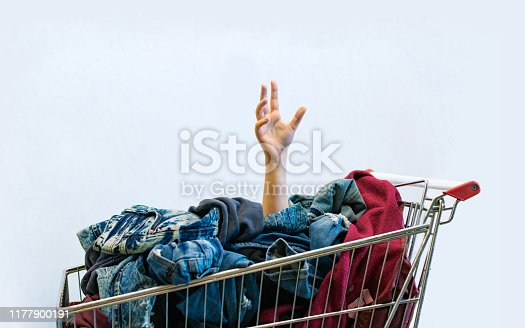 istock Shopaholic concept. Female hand sticks out of shopping cart 1177900191