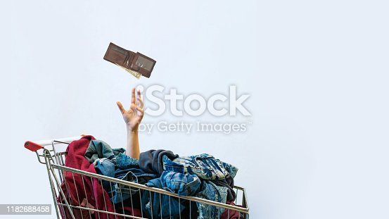 istock Shopaholic concept. Female hand sticks out of shopping cart 1182688458