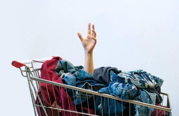 shopaholic concept. vrouwelijke hand stokken uit de winkelwagen vol kleren. oncontroleerbare shopping - compulsieve stoornis of oniomanie kopen. kopieer ruimte. - shopaholic stockfoto's en -beelden