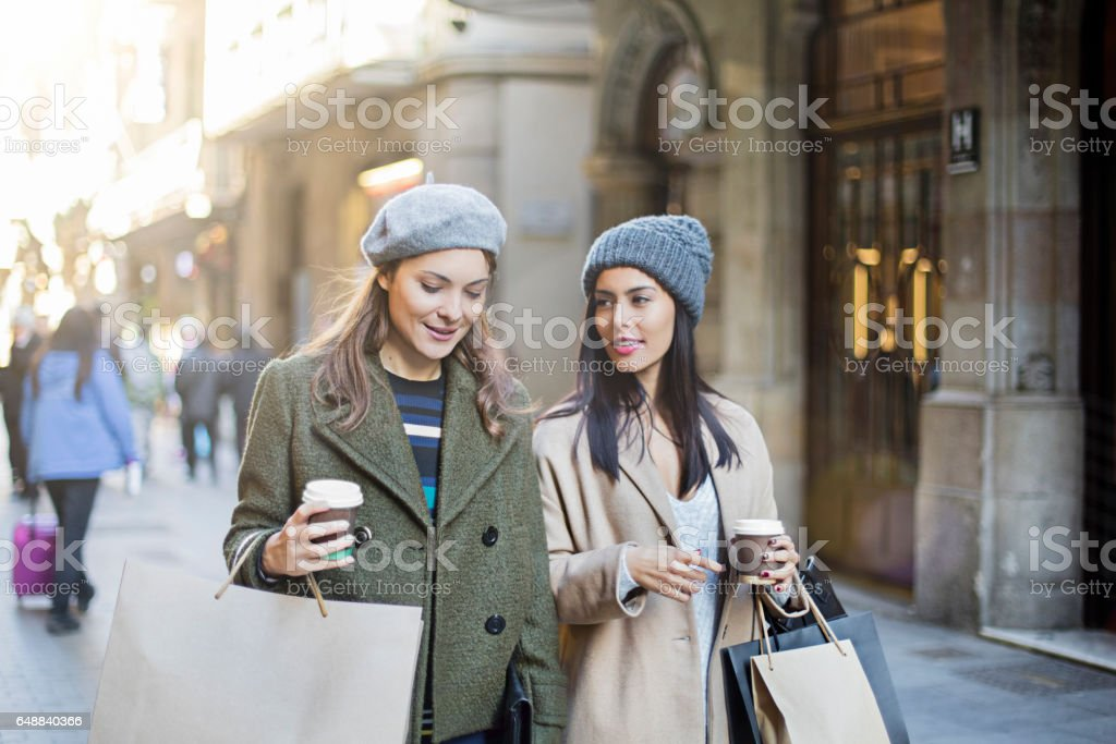 Shopaholic female friends talking on sidewalk - foto de acervo