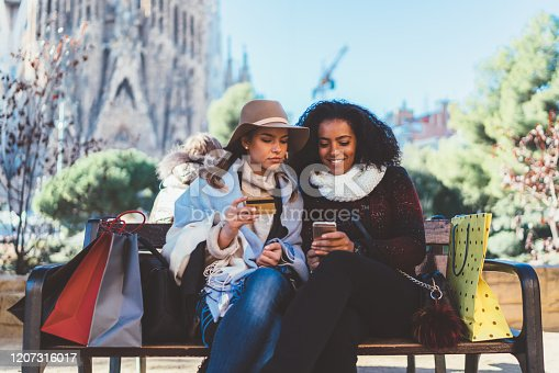 Young women in the city park making an online reservation with credit card