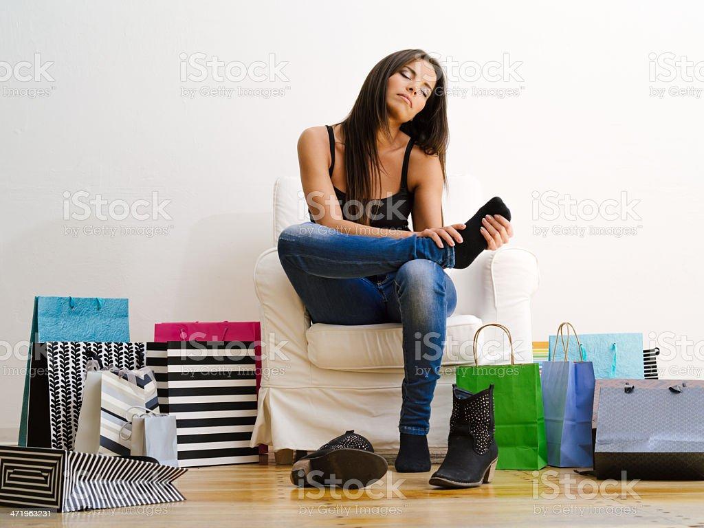 Shopaholic rubbing her tired feet stock photo