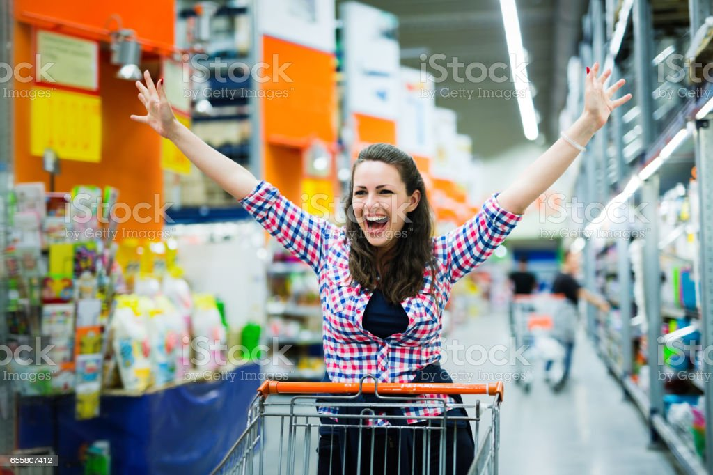 Shopaholic woman enjoying shopping spree in supermarket stock photo