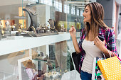 Young woman in the shopping mall enjoying jewellery on the shop window