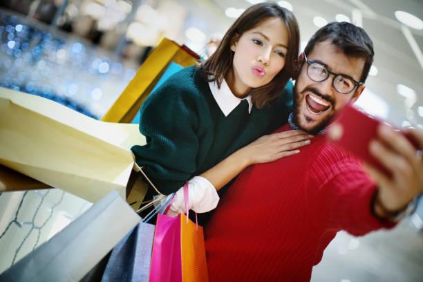shopaholics. - brunette woman eyeglasses kiss man foto e immagini stock