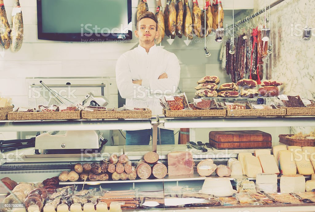 Shop-boy in special clothing shifting sausage stock photo