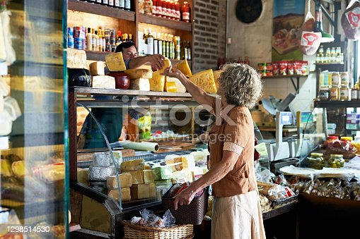 Partial view of businessman in early 40s wearing apron and reaching across display case to hand woman cheese selection in Argentine gourmet grocery store.