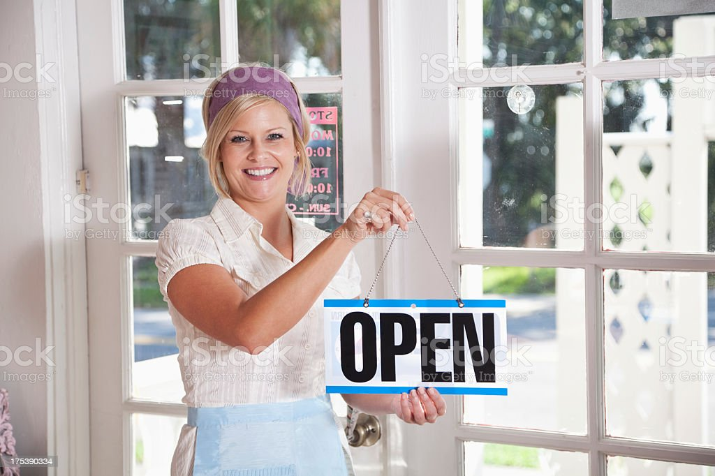Shopkeeper holding open sign stock photo