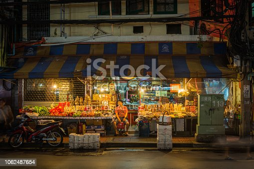 Shopkeeper waiting for customers at his roadside grocery shop illuminated at night in Bangkok's Chinatown, Thailand.