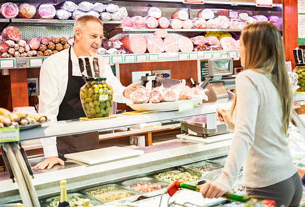 shopkeeper serving a customer - delis stock photos and pictures