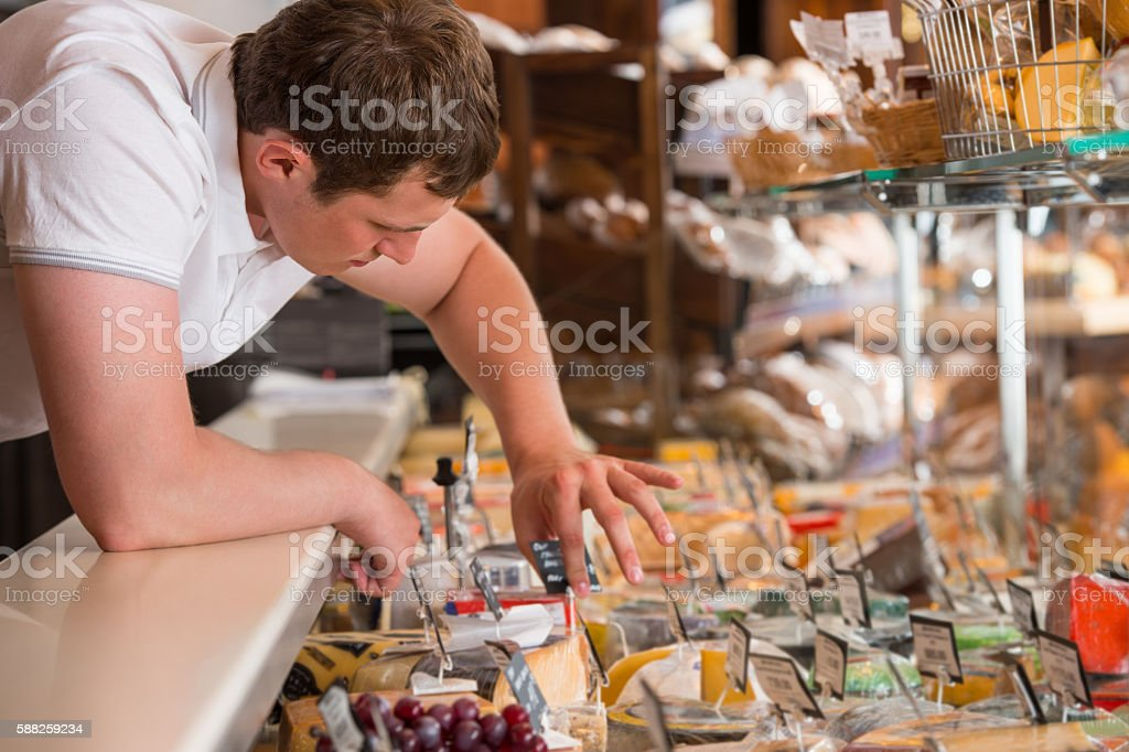 Shopkeeper working in cheese glass case in grocery store stock photo