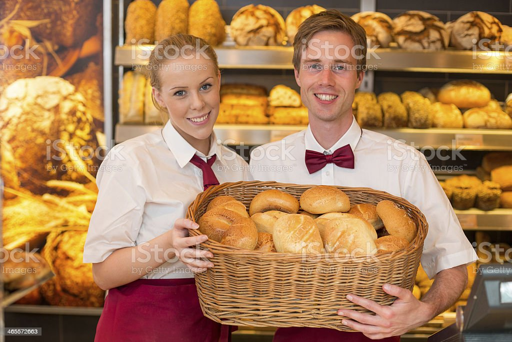 Shopkeepers at baker's shop presenting buns in a basket royalty-free stock photo