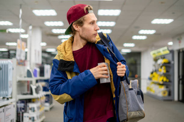 shoplifter in the electronic store supermarket stealing new gadget f shoplifter in the electronic store supermarket stealing new gadget thief stock pictures, royalty-free photos & images