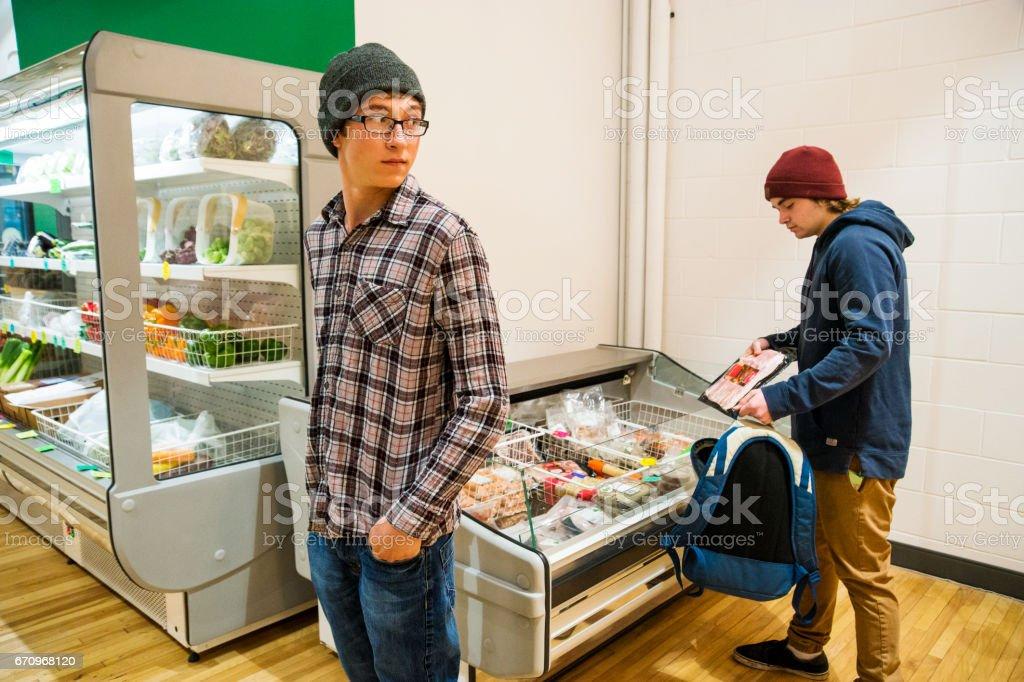 Shoplifting teens stealing bacon stock photo