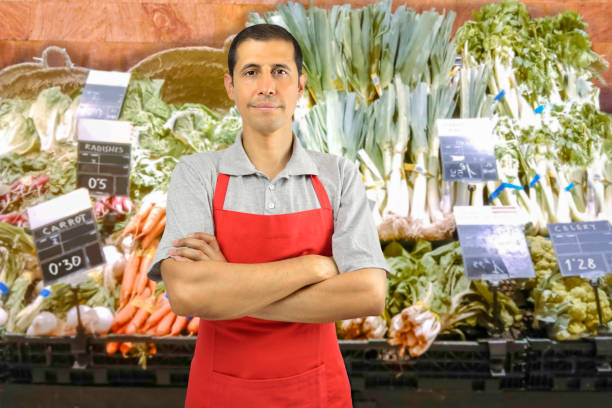 shopman at the greengrocer portrait of shopman at the vegetables store with crossing arms grocer stock pictures, royalty-free photos & images