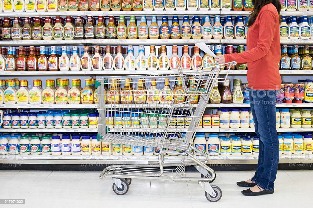 Shopper checking list in supermarket aisle stock photo