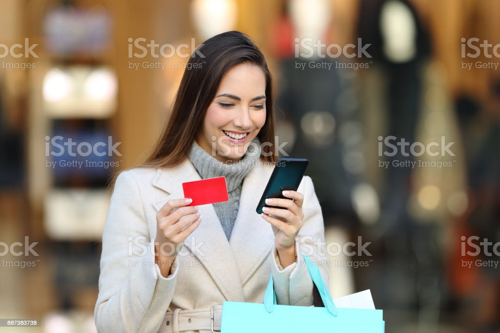 Shopper holding shopping bags paying on line - foto stock