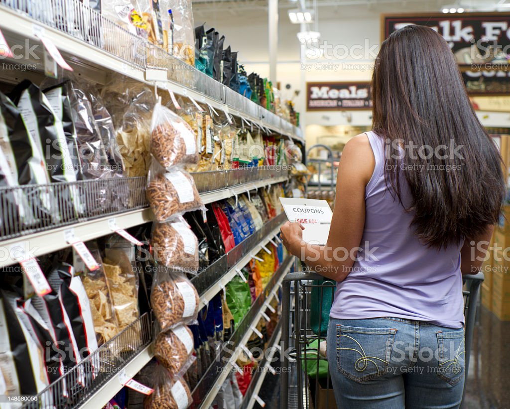 Shopper in Store Looks at Coupon royalty-free stock photo