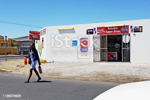 Cape Town, South Africa - December 16, 2019: A shopper carrying her purchases leaves a small convenience store in the lower-middle-class suburb of Grassy Park. Such shops, typically operated by recent immigrants from the Indian subcontinent or countries further north in Africa, have mushroomed across South Africa in recent decades.