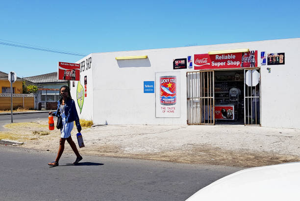 Shopper leaving tiny Cape Town convenience store carrying purchases stock photo