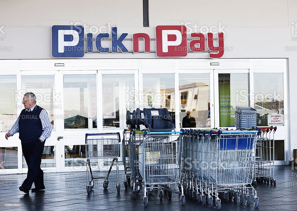 Shopper passing the entrance to Pick n Pay supermarket branch royalty-free stock photo