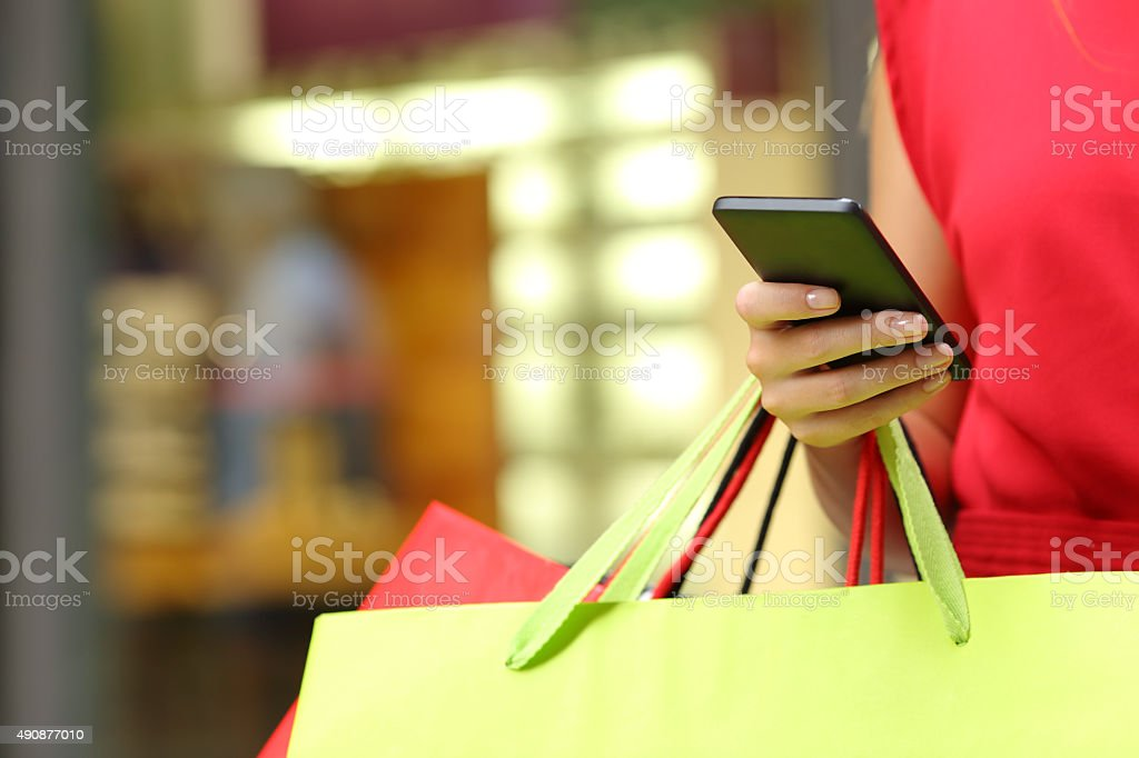 Shopper shopping with a smart phone Shopper woman hand shopping with a smart phone and carrying bags 2015 Stock Photo