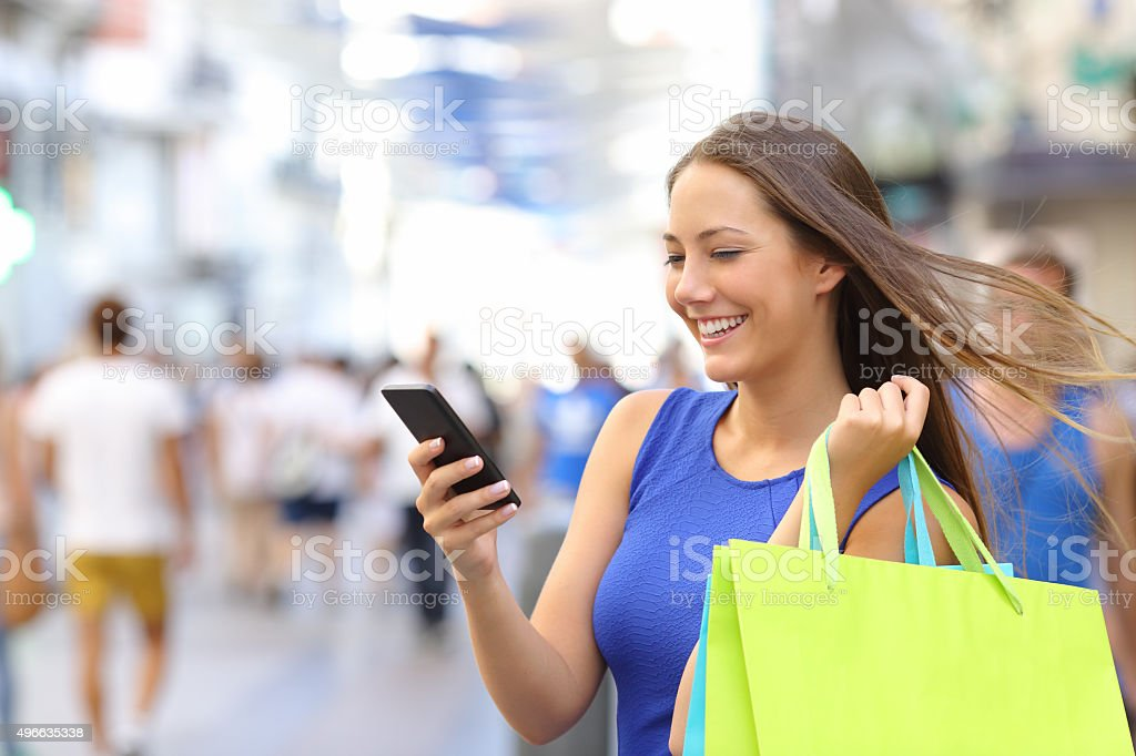 Shopper shopping with smartphone in the street stock photo