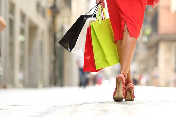 shopper woman legs walking with shopping bags - kleider günstig kaufen stock-fotos und bilder